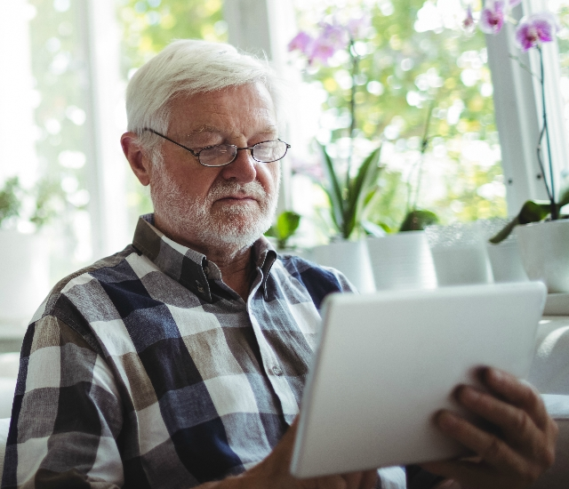Photo of an older man using a tablet device